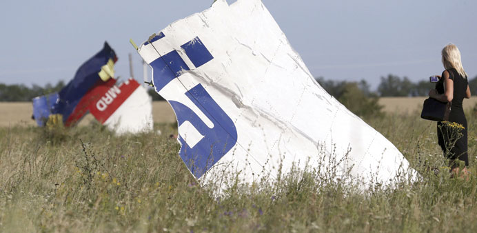 A woman takes a photograph of the wreckage at the crash site of Malaysia Airlines Flight MH17 near t