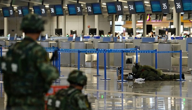 A paramilitary bomb disposal expert (background R) inspects luggage left near a check-in counter aft