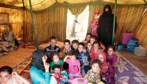 Iraqi women and children, who fled the ongoing fighting in the Fallujah area, sit inside a tent at a