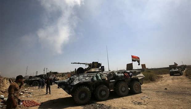 Members of Iraqi government force gather next to their vehicles during an operation in Fallujah