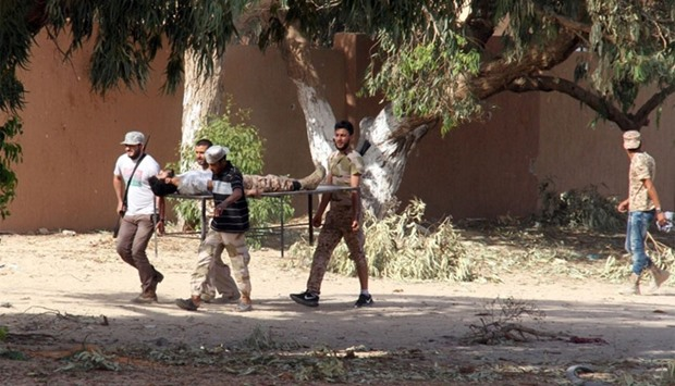 Forces loyal to Libya's UN-backed unity government carry a comrade wounded in Sirte