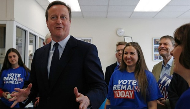 Britain's Prime Minister David Cameron gestures while speaking with campaign volunteers