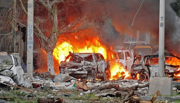 Wrecked cars burn at the scene of a terror attack at the Ambassador Hotel, after a car bomb exploded