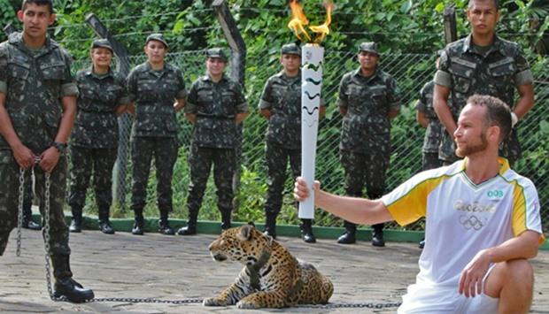An athlete holds the Olympic Torch by a jaguar --symbol of Amazonia-- during a ceremony in Manaus