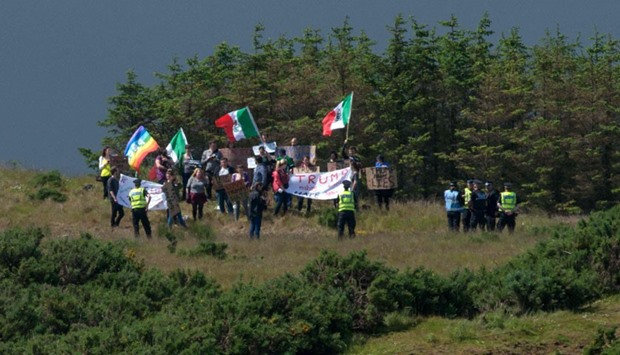A group of protesters wave Mexican flags on the hillside above the Trump International Golf Links