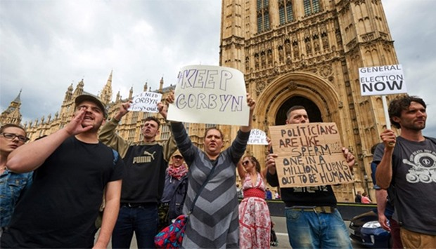 Demonstrators hold up placards as they protest outside the British Parliament in central London