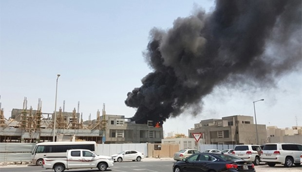 Smoke rises from the fire that broke out on the rooftop of an under-construction villa in the Al Hil