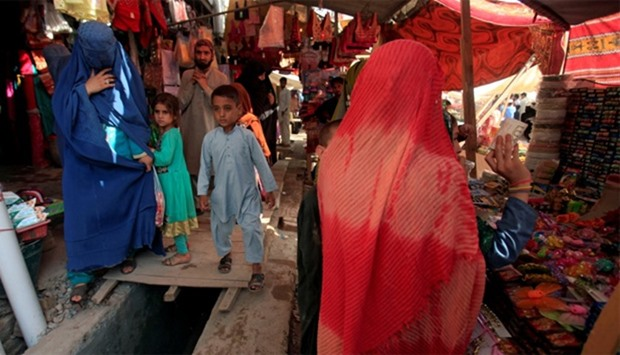 An Afghan woman, clad in a burqa, shops at a market in Peshawar, Pakistan