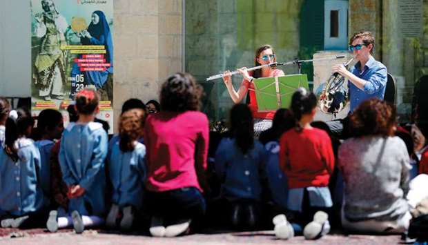 Two musicians perform in front of Palestinian schoolchildren during a festival organised by Palestin