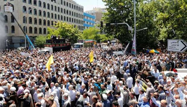 Iranians march during the funeral of the victims of the attacks on Tehran's parliament complex and s