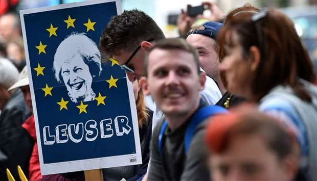 A demonstrator holds a placard depicting an image of Britain's Prime Minister Theresa May