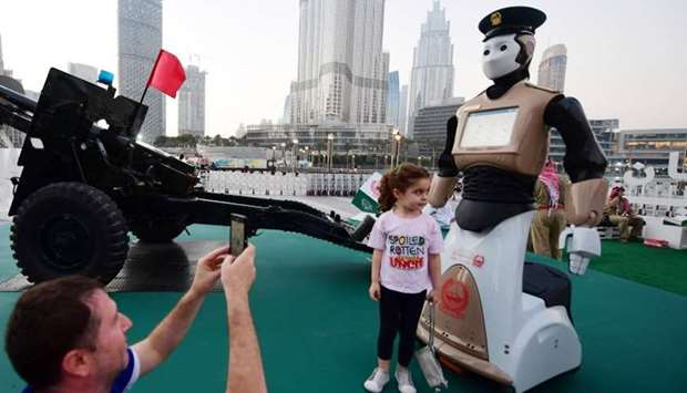 People take a picture with the world's first operational police robot near the Burj Khalifa