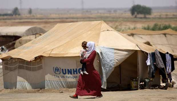 A Syrian woman displaced from Raqa walks carrying a child at the al-Karamah aid camp