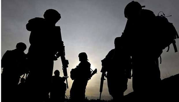US soldiers with the NATO-led International Security Assistance Force (ISAF) silhouetted as they wal