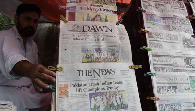 A Pakistani vendor arranges morning newspapers featuring front page coverage of Pakistan's victory a