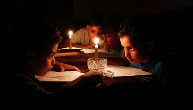 Palestinian children at home reading books by candle light due to electricity shortages in Gaza City