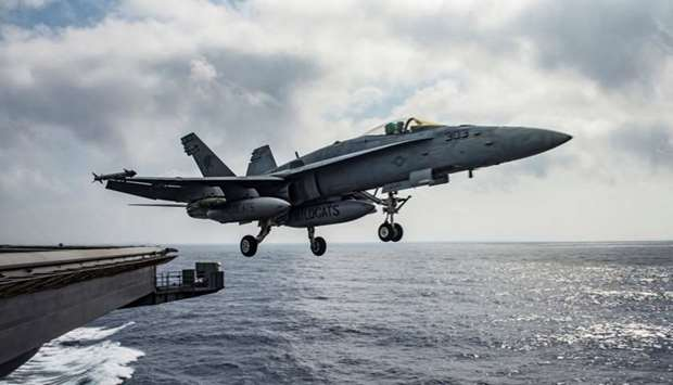 A US Navy F/A-18E Super Hornet launches from the flight deck of the aircraft carrier USS Dwight D. E