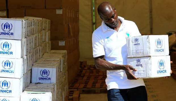 A social worker arranges emergency utensil boxes at the United Nations High Commissioner for Refugee