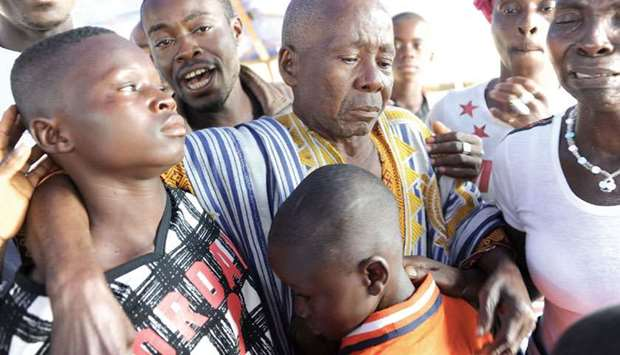 Exiled Ivorian children Hurbain Souomi (left) and Thierry Souomi are hugged by their grandfather Lah