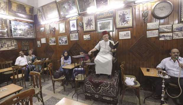 Ahmad al-Lahham, a Syrian storyteller, reads from his storybook in a Damascus coffee house.
