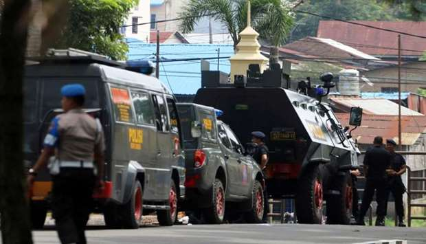 Police are seen near the scene of an attack on a post that left one officer dead in Medan