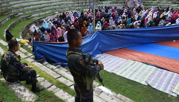 Members of the police special action force stand guard as Muslims, who fled the conflict in Marawi,