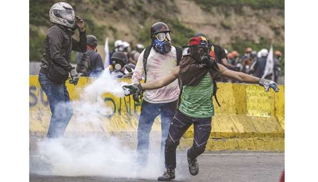 An opposition activist throws teargas back at riot police in clashes at the Francisco de Miranda air