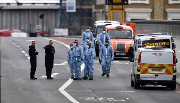 Police forensic investigators works on London Bridge after an attack left 7 people dead and dozens i