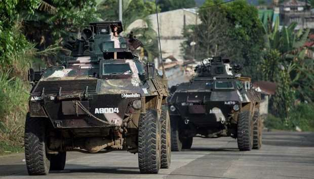 Armoured personnel carriers drive down a village road in Marawi