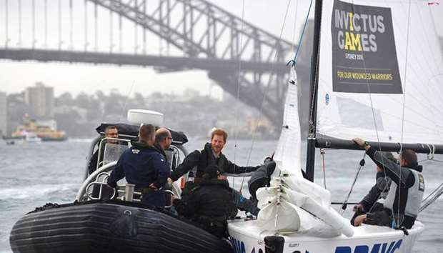 Britain's Prince Harry holds onto a yacht during a sailing demonstration