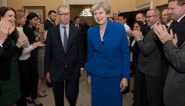 Britain's Prime Minister Theresa May and her husband Philip are welcomed by staff inside 10 Downing