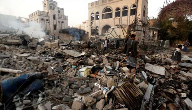 Guards walk on the wreckage of a building destroyed by air strikes in Sanaa, Yemen on June 6, 2018.