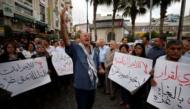 Palestinians take part in a protest demanding to lift the sanctions on Gaza Strip, in Ramallah, in t
