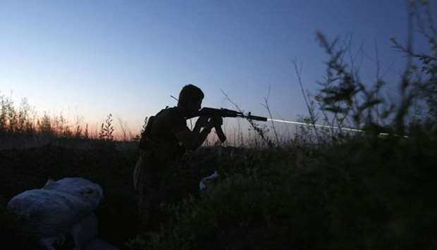 A Ukrainian serviceman fires his gun in the direction of Russia-backed separatists during night comb
