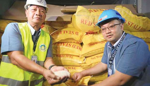 Customs Commissioner Isidro Lapena presents a container with sacks of smuggled Thailand white rice,