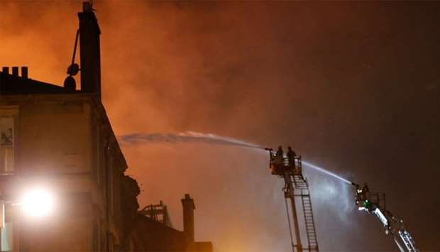 Firefighters attend to a blaze at the Mackintosh Building at the Glasgow School of Art, which is the