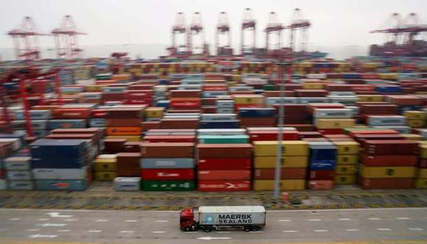 A container truck moves past containers at the Yangshan Deep Water Port in Shanghai
