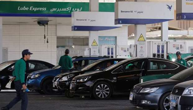 Workers fill cars as people queue and wait in their cars at a petrol stations after an increase in f