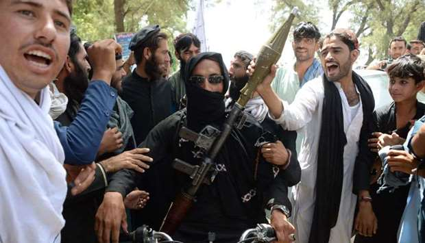 An Afghan Taliban militants carries a rocket-propelled as he looks on with residents as they took to