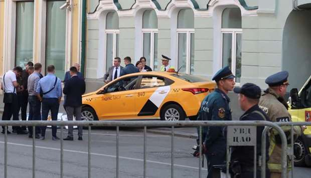 Investigators and members of emergencies services gather near a damaged taxi, which ran into a crowd