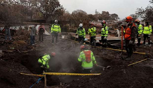 Rescue workers search for missing families at the area affected by the Fuego volcano at San Miguel L