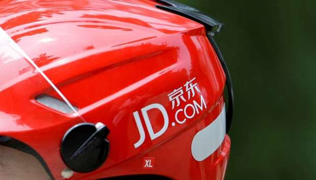 A logo of JD.com is seen on a helmet of a delivery man in Beijing, China