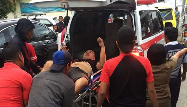 A survivor been taken away in an ambulance after a boat overturned in Lake Toba in the province of N