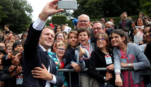 French President Emmanuel Macron makes selfie with children