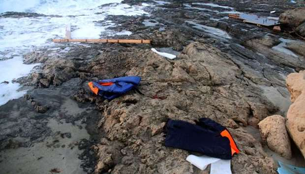 Life jackets are seen on the beach as Libyan Red Crescent team members recover bodies of migrants wh
