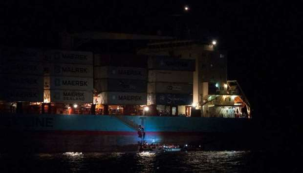 Migrants boarding a container ship of Danish shipping company Maersk Line after they were rescued fr