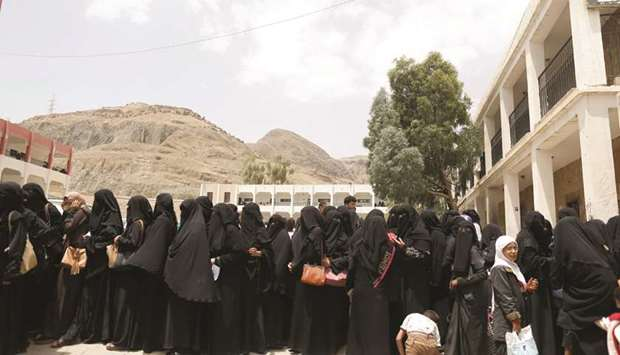 Women displaced by the fighting in the Red Sea port city of Hodeidah queue to register in a school a