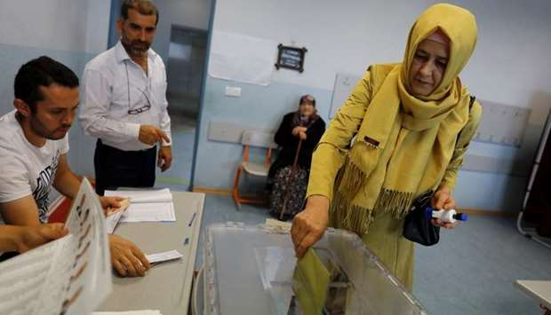 A woman casts his ballot during Turkey's presidential and parliamentary elections at a polling stati