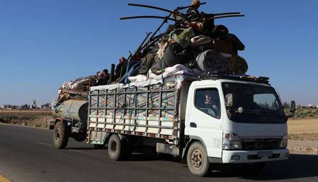 People ride on a truck loaded with belongings in Deraa countryside