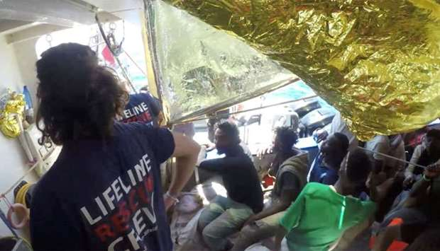 Migrants and crew are seen on the ship Lifeline while the Malta Armed Forces deliver aid, near Malta